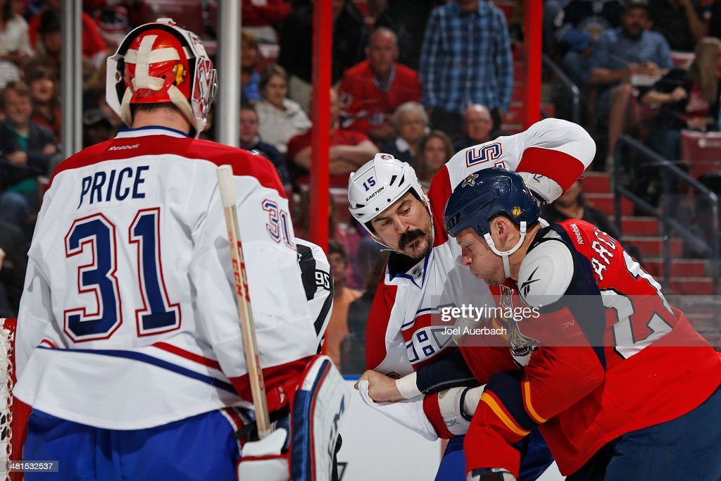 Goaltender Carey Price looks on as George Parros of the Montreal Canadiens squares off against Krys Barch of the Florida Panthers at the BBT Center...