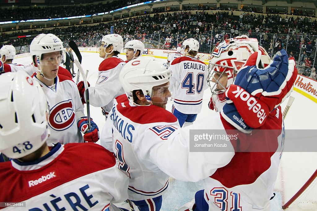 Goaltender <a gi-track='captionPersonalityLinkClicked' href=/galleries/search?phrase=Carey+Price&family=editorial&specificpeople=2222083 ng-click='$event.stopPropagation()'>Carey Price</a> #31 of the Montreal Canadiens gets congratulated by teammates after backstopping the team to a 3-0 victory over the Winnipeg Jets at the MTS Centre on October 15, 2013 in Winnipeg, Manitoba, Canada.