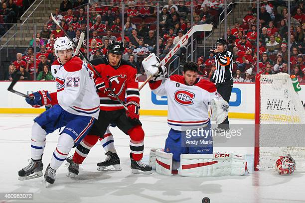 Goaltender Carey Price of the Montreal Canadiens playing in his 400th NHL game loses his mask after being hit with a shot as Nathan Beaulieu is...