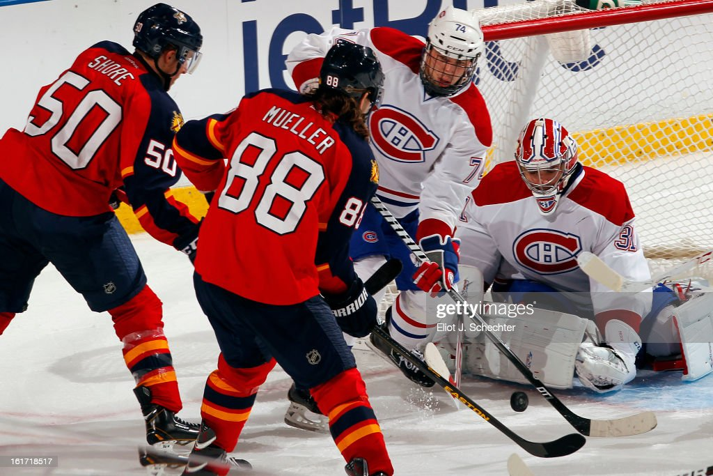 Goaltender <a gi-track='captionPersonalityLinkClicked' href=/galleries/search?phrase=Carey+Price&family=editorial&specificpeople=2222083 ng-click='$event.stopPropagation()'>Carey Price</a> #31of the Montreal Canadiens defends the net against Peter Mueller #88 and Drew Shore #50 of the Florida Panthers at the BB&T Center on February 14, 2013 in Sunrise, Florida.