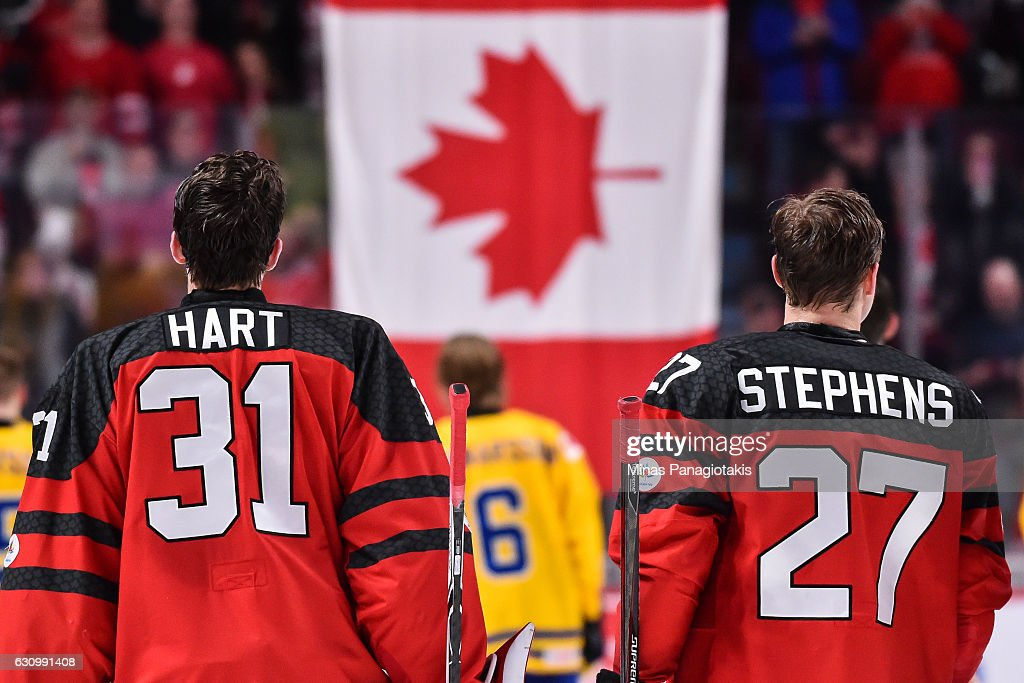 Goaltender Carter Hart #31 and teammate Mitchell Stephens #27 of Team Canada watch as the Canadian flag is raised after defeating Team Sweden and move to the gold medal round during the 2017 IIHF World Junior Championship semifinal game at the Bell Centre on January 4, 2017 in Montreal, Quebec, Canada. Team Canada defeated Team Sweden 5-2.