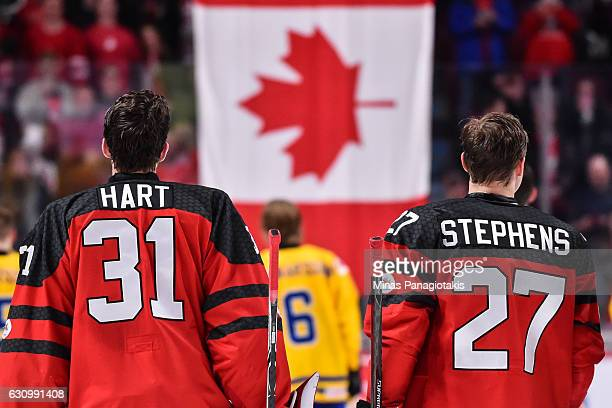 Goaltender Carter Hart and teammate Mitchell Stephens of Team Canada watch as the Canadian flag is raised after defeating Team Sweden and move to the...
