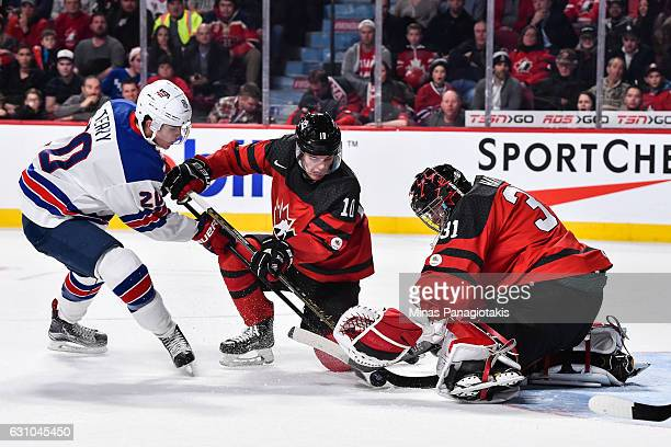 Goaltender Carter Hart of Team Canada tries to cover the puck while teammate Kale Clague defends against Troy Terry of Team United States during the...