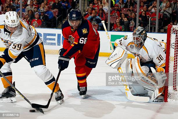 Goaltender Carter Hutton of the Nashville Predators defends the net with the help of teammate Roman Josi against Jaromir Jagr of the Florida Panthers...