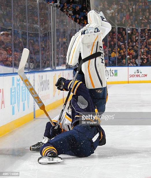 Goaltender Carter Hutton of the Nashville Predators is upended by Marcus Foligno as they chase a loose puck during the third period of their NHL game...