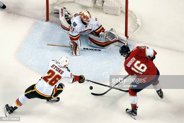 Goaltender Chad Johnson of the Calgary Flames defends the net with the help of teammate Michael Stone against Aleksander Barkov of the Florida...