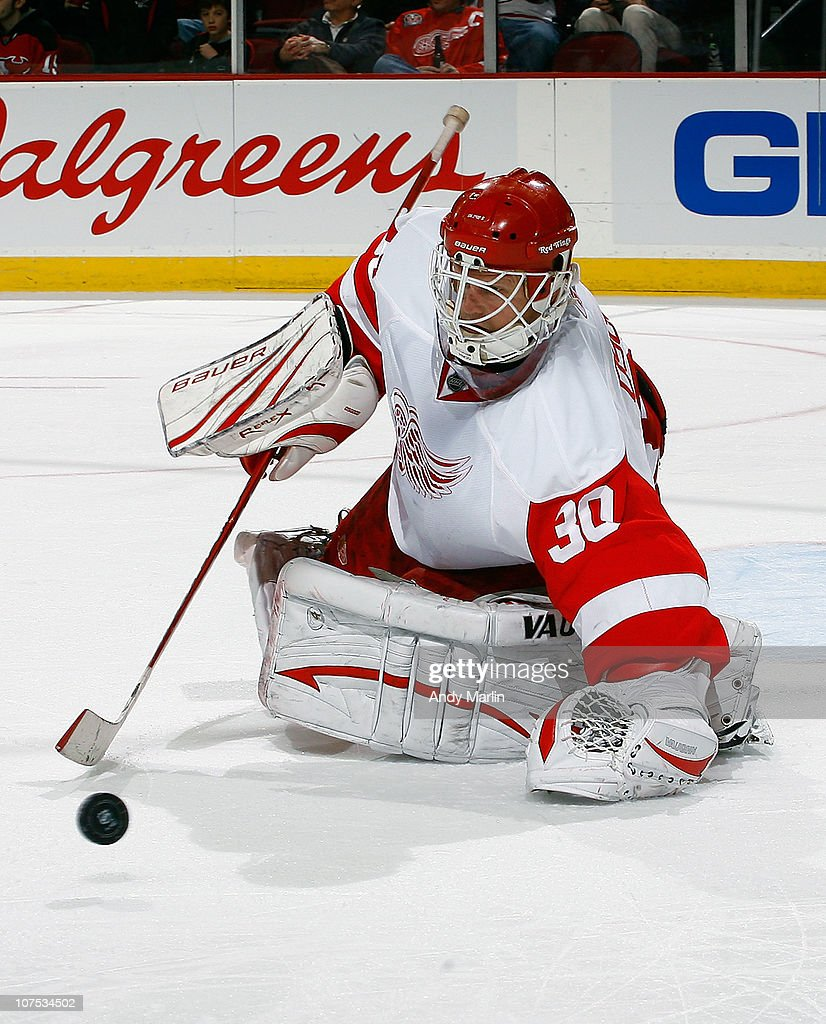 Goaltender Chris Osgood #30 of the Detroit Red Wings makes a save on his way to defeating the New Jersey Devils at the Prudential Center on December 11, 2010 in Newark, New Jersey. The Red Wings defeated the Devils 4-1.
