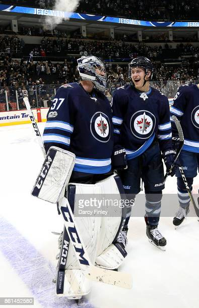 Goaltender Connor Hellebuyck and Andrew Copp of the Winnipeg Jets share a laugh as they leave the ice following a 21 victory over the Carolina...