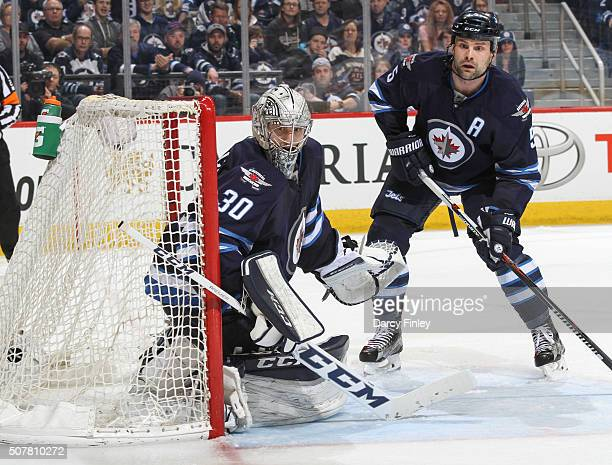 Goaltender Connor Hellebuyck and Mark Stuart of the Winnipeg Jets keep an eye on the play behind the net during third period action against the...