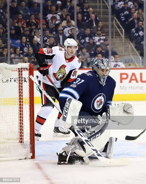 Goaltender Connor Hellebuyck of the Winnipeg Jets and Matt Duchene of the Ottawa Senators keep an eye on the play during third period action at the...