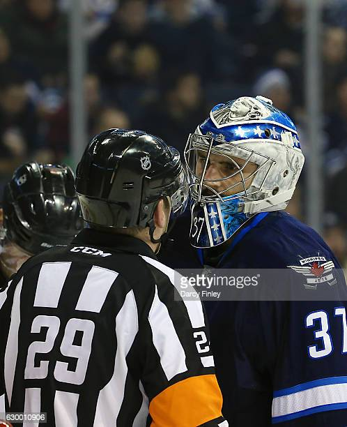 Goaltender Connor Hellebuyck of the Winnipeg Jets chats with referee Ian Walsh during a first period stoppage in play against the Florida Panthers at...