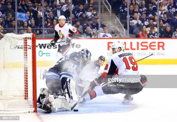 Goaltender Connor Hellebuyck of the Winnipeg Jets gets a pad out to stop a shot by Derick Brassard of the Ottawa Senators during third period action...