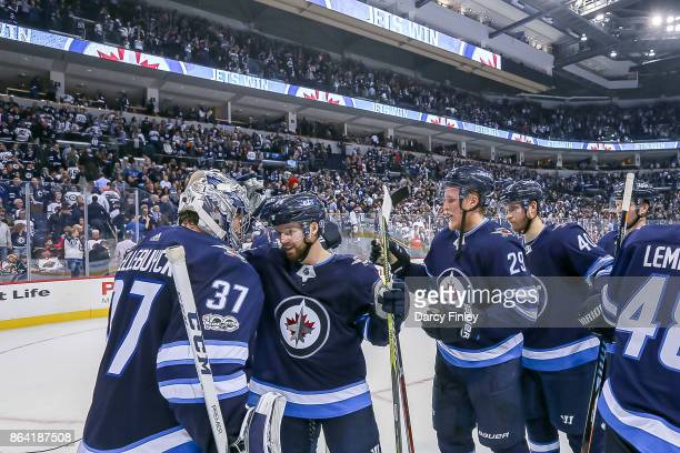 Goaltender Connor Hellebuyck of the Winnipeg Jets gets congratulated by teammates following a 43 victory over the Minnesota Wild at the Bell MTS...