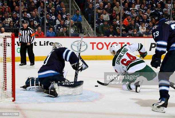 Goaltender Connor Hellebuyck of the Winnipeg Jets guards the net as Mikael Granlund of the Minnesota Wild plays the puck from his knees during first...