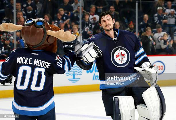 Goaltender Connor Hellebuyck of the Winnipeg Jets is all smiles as he celebrates a 30 shutout victory over the St Louis Blues with team mascot Mick E...