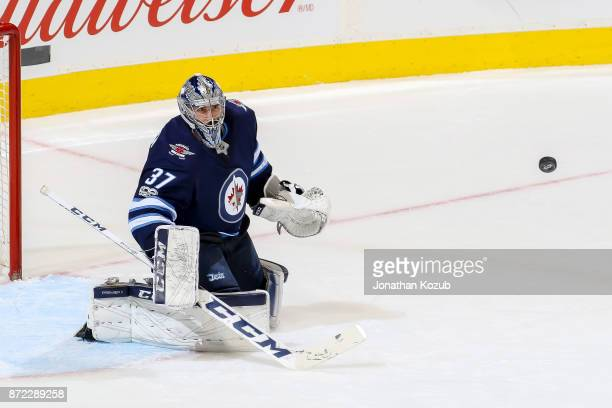 Goaltender Connor Hellebuyck of the Winnipeg Jets keeps an eye on the flying puck during second period action against the Montreal Canadiens at the...