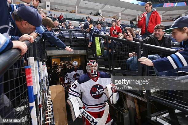 Goaltender Connor Hellebuyck of the Winnipeg Jets leads the team to the ice for the start of the pregame warm up prior to NHL action against the...