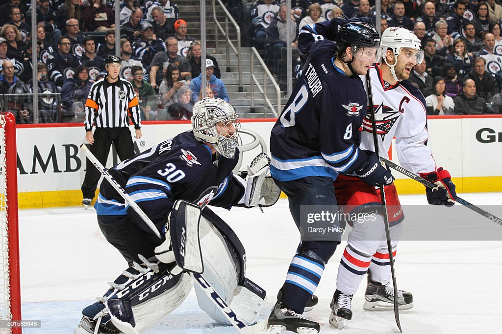 Goaltender <a gi-track='captionPersonalityLinkClicked' href=/galleries/search?phrase=Connor+Hellebuyck&family=editorial&specificpeople=10551764 ng-click='$event.stopPropagation()'>Connor Hellebuyck</a> #30 of the Winnipeg Jets looks around a screen set by teammate <a gi-track='captionPersonalityLinkClicked' href=/galleries/search?phrase=Jacob+Trouba&family=editorial&specificpeople=8050718 ng-click='$event.stopPropagation()'>Jacob Trouba</a> #8 as he battles <a gi-track='captionPersonalityLinkClicked' href=/galleries/search?phrase=Nick+Foligno&family=editorial&specificpeople=537821 ng-click='$event.stopPropagation()'>Nick Foligno</a> #71 of the Columbus Blue Jackets during third period action at the MTS Centre on December 10, 2015 in Winnipeg, Manitoba, Canada. The Jets defeated the Jackets 6-4.