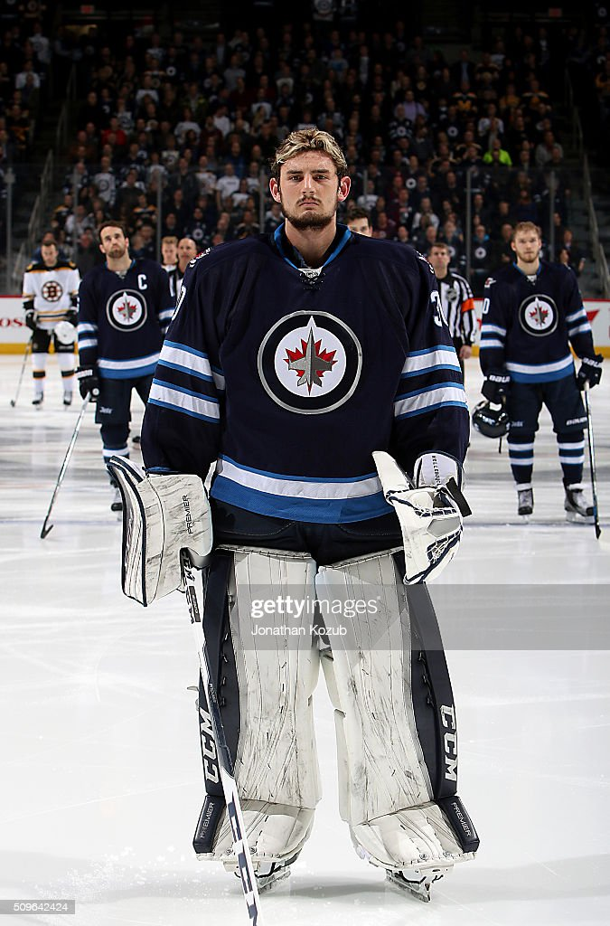Goaltender <a gi-track='captionPersonalityLinkClicked' href=/galleries/search?phrase=Connor+Hellebuyck&family=editorial&specificpeople=10551764 ng-click='$event.stopPropagation()'>Connor Hellebuyck</a> #30 of the Winnipeg Jets looks on during the singing of the National anthems prior to puck drop against the Boston Bruins at the MTS Centre on February 11, 2016 in Winnipeg, Manitoba, Canada.