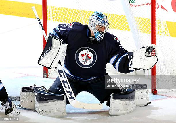 Goaltender Connor Hellebuyck of the Winnipeg Jets makes a glove save during third period action against the Colorado Avalanche at the MTS Centre on...