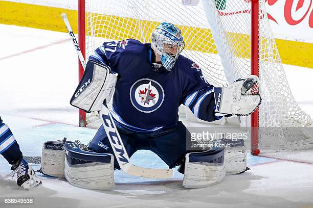 Goaltender Connor Hellebuyck of the Winnipeg Jets makes a glove save against the Colorado Avalanche during third period action at the MTS Centre on...