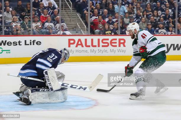 Goaltender Connor Hellebuyck of the Winnipeg Jets makes a save as Landon Ferraro of the Minnesota Wild looks for a rebound during first period action...