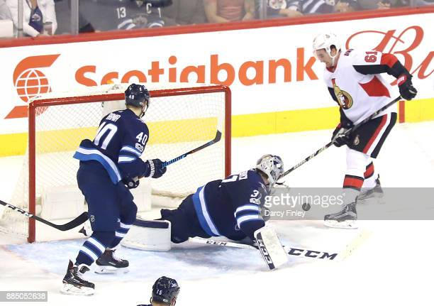 Goaltender Connor Hellebuyck of the Winnipeg Jets makes a save on Mark Stone of the Ottawa Senators during second period action at the Bell MTS Place...
