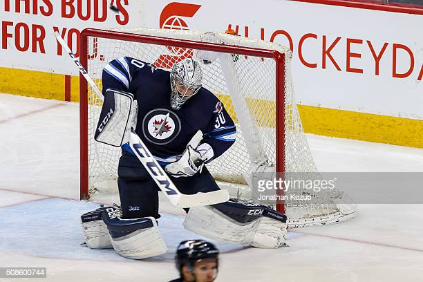 Goaltender Connor Hellebuyck of the Winnipeg Jets makes a shoulder save and deflects the puck wide during third period action against the Dallas...