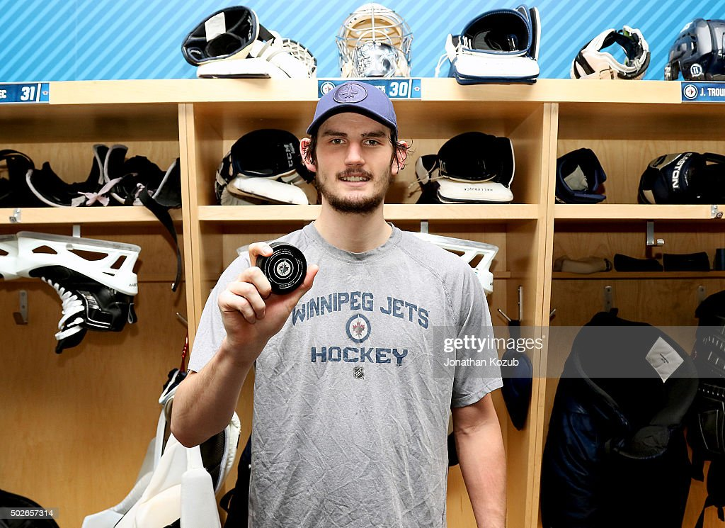 Goaltender <a gi-track='captionPersonalityLinkClicked' href=/galleries/search?phrase=Connor+Hellebuyck&family=editorial&specificpeople=10551764 ng-click='$event.stopPropagation()'>Connor Hellebuyck</a> #30 of the Winnipeg Jets shows off the game puck following a 1-0 victory over the Pittsburgh Penguins at the MTS Centre on December 27, 2015 in Winnipeg, Manitoba, Canada. This is Hellebuyck's first career NHL shutout.