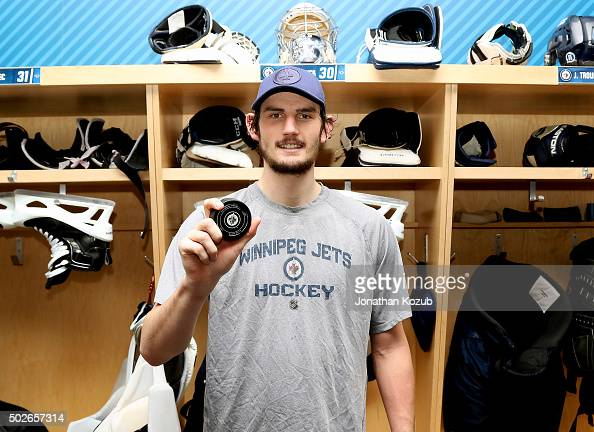 Goaltender Connor Hellebuyck of the Winnipeg Jets shows off the game puck following a 10 victory over the Pittsburgh Penguins at the MTS Centre on...