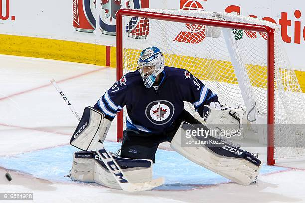 Goaltender Connor Hellebuyck of the Winnipeg Jets slides across the crease to make a save during third period action against the Boston Bruins at the...