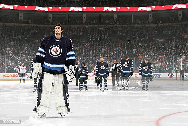 Goaltender Connor Hellebuyck of the Winnipeg Jets stands on the ice with teammates during the singing of 'O Canada' prior to puck drop against the...