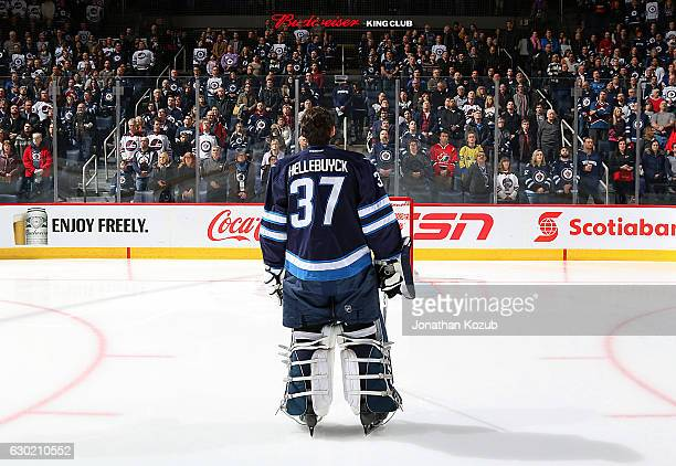 Goaltender Connor Hellebuyck of the Winnipeg Jets stands on the ice during the singing of the National anthems prior to puck drop against the...