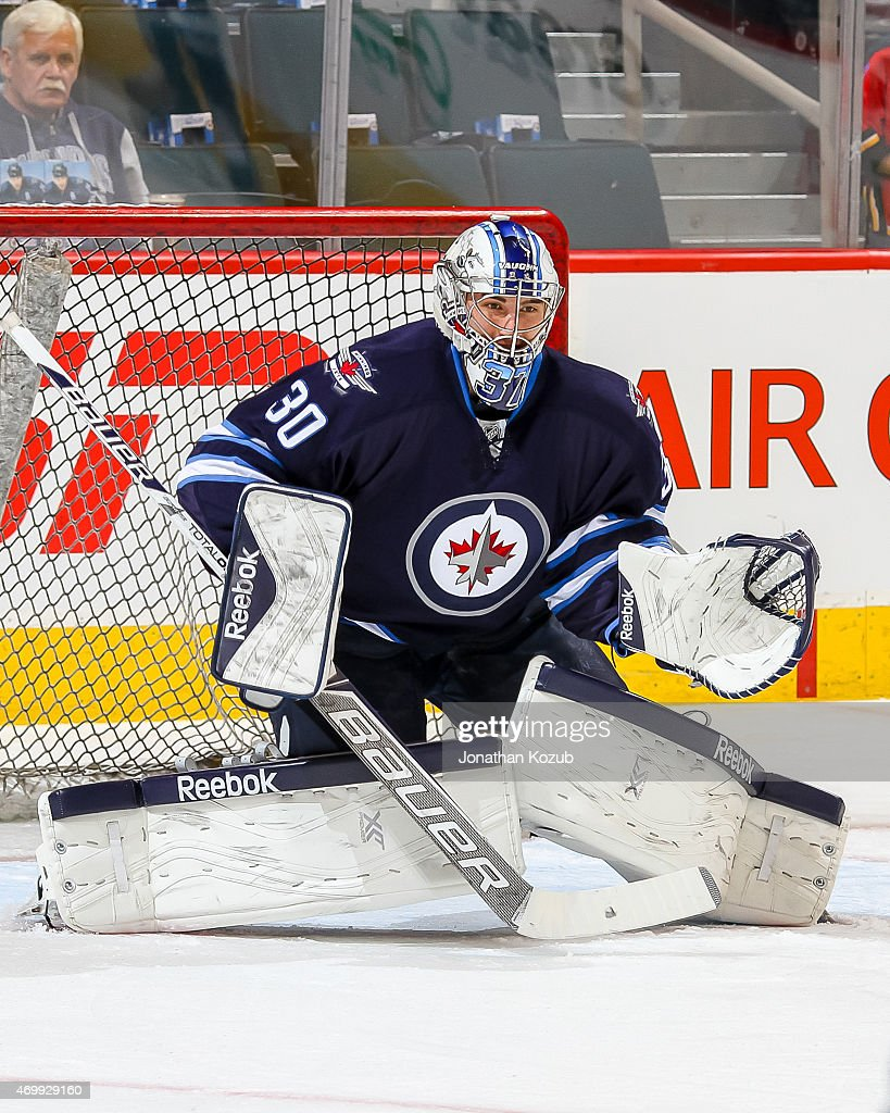 Goaltender <a gi-track='captionPersonalityLinkClicked' href=/galleries/search?phrase=Connor+Hellebuyck&family=editorial&specificpeople=10551764 ng-click='$event.stopPropagation()'>Connor Hellebuyck</a> #30 of the Winnipeg Jets takes part in the pre-game warm up prior to NHL action against the Calgary Flames on April 11, 2015 at the MTS Centre in Winnipeg, Manitoba, Canada.