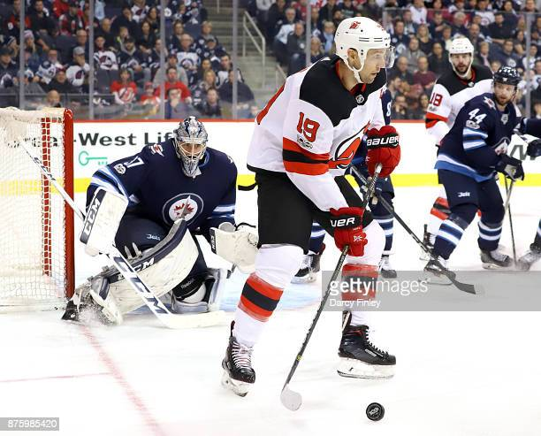 Goaltender Connor Hellebuyck of the Winnipeg Jets watches as Travis Zajac of the New Jersey Devils plays the puck during third period action at the...