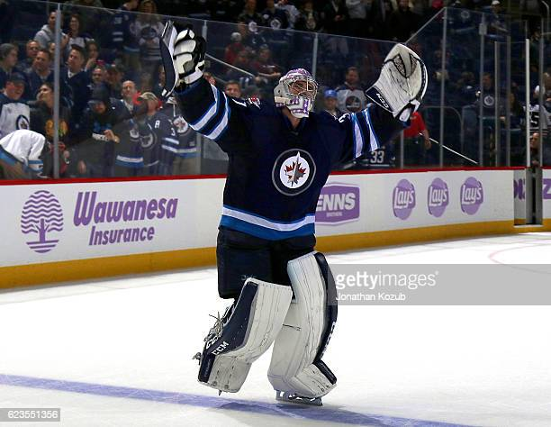 Goaltender Connor Hellebuyck raises his arms in celebration after being named the first star of the game following a 40 shutout over the Chicago...