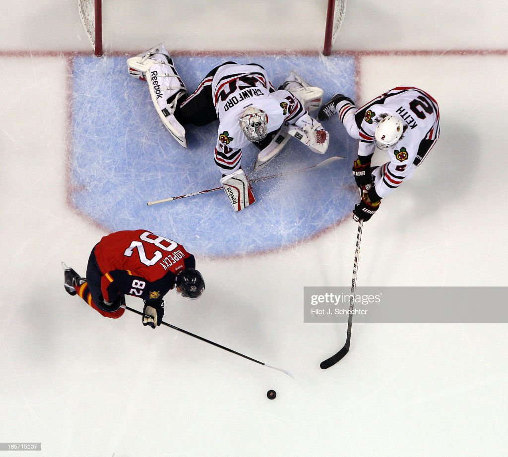 Goaltender Corey Crawford #50 of the Chicago Blackhawks defends the net with the help of teammate Duncan Keith #2 against Tomas Kopecky #82 of the Florida Panthers at the BB&T Center on October 22, 2013 in Sunrise, Florida.