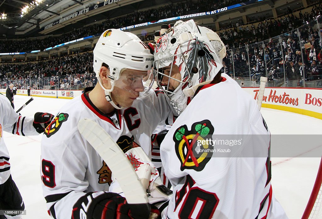 Goaltender Corey Crawford #50 of the Chicago Blackhawks gets congratulated by teammate Jonathan Toews #19 after backstopping the team to a 5-1 victory over the Winnipeg Jets at the MTS Centre on November 2, 2013 in Winnipeg, Manitoba, Canada.