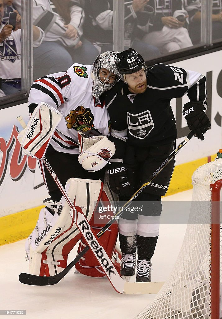 Goaltender Corey Crawford #50 of the Chicago Blackhawks is checked by Trevor Lewis #22 of the Los Angeles Kings in the first period in Game Six of the Western Conference Final during the 2014 Stanley Cup Playoffs at Staples Center on May 30, 2014 in Los Angeles, California.