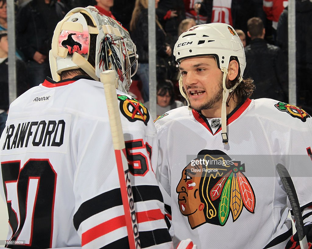 Goaltender Corey Crawford #50 of the Chicago Blackhawks is congratulated by teammate Daniel Carcillo #13 after an NHL game against the Detroit Red Wings at Joe Louis Arena on March 3, 2013 in Detroit, Michigan. Chicago won 2-1 in a shoot-out
