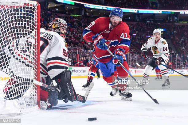 Goaltender Corey Crawford of the Chicago Blackhawks tries to get into position while Paul Byron of the Montreal Canadiens skates for the puck during...