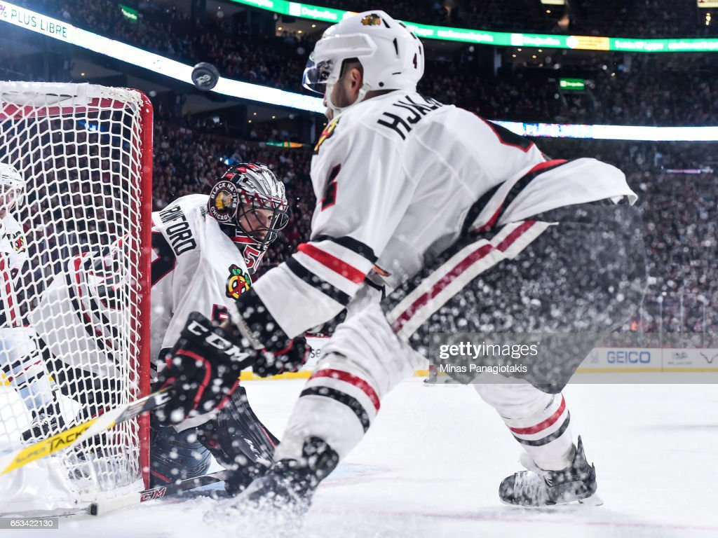 Goaltender Corey Crawford #50 of the Chicago Blackhawks watches the puck as teammate Niklas Hjalmarsson #4 skates in during the NHL game against the Montreal Canadiens at the Bell Centre on March 14, 2017 in Montreal, Quebec, Canada. The Chicago Blackhawks defeated the Montreal Canadiens 4-2.