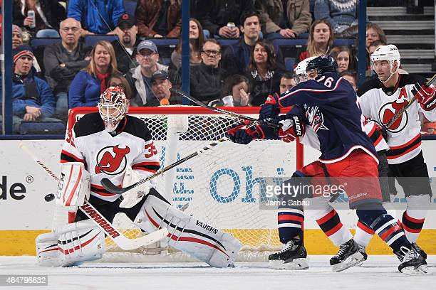 Goaltender Cory Schneider of the New Jersey Devils defends the net as Corey Tropp of the Columbus Blue Jackets attempts to redirect the puck during...