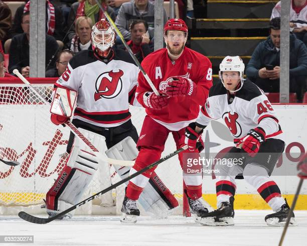 Goaltender Cory Schneider of the New Jersey Devils follows the play as teammate Karl Stollery defends against Justin Abdelkader of the Detroit Red...