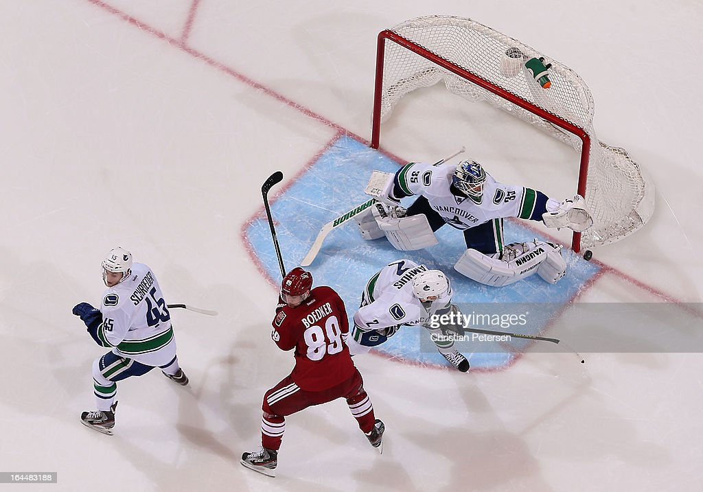 Goaltender <a gi-track='captionPersonalityLinkClicked' href=/galleries/search?phrase=Cory+Schneider&family=editorial&specificpeople=696908 ng-click='$event.stopPropagation()'>Cory Schneider</a> #35 of the Vancouver Canucks attempts to cover the puck during the NHL game against the Phoenix Coyotes at Jobing.com Arena on March 21, 2013 in Glendale, Arizona. The Canucks defeated the Coyotes 2-1.