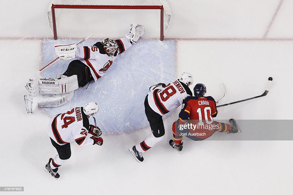Goaltender Cory Schneider stretches to protect the post as Anton Volchenkov of the New Jersey Devils pokes the puck away from Joey Crabb of the...