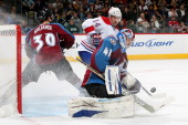 Goaltender Craig Anderson of the Colorado Avalanche makes a save against the Montreal Canadiens as TJ Galiardi defends against Tomas Plakanec at the...