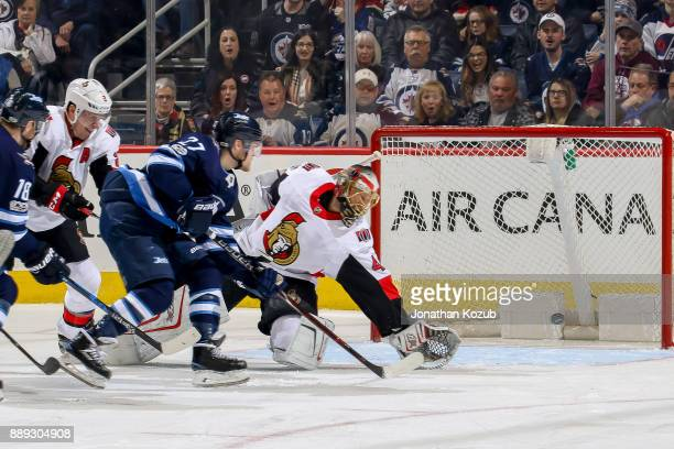 Goaltender Craig Anderson of the Ottawa Senators deflects the puck with his glove just past the net to deny Nikolaj Ehlers of the Winnipeg Jets...