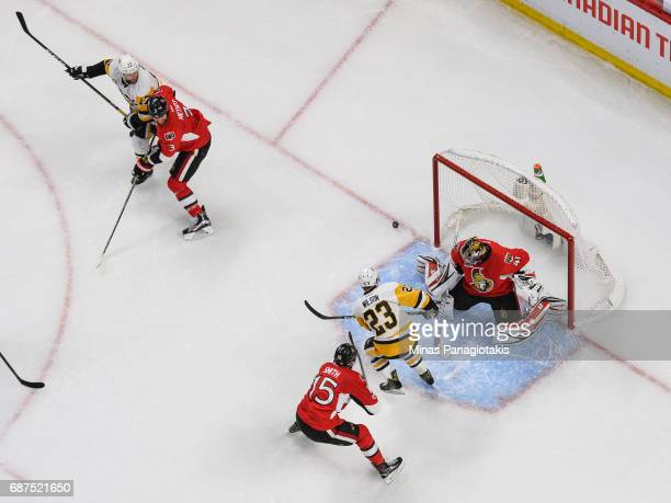 Goaltender Craig Anderson of the Ottawa Senators makes a pad save while teammate Zack Smith defends against Scott Wilson of the Pittsburgh Penguins...
