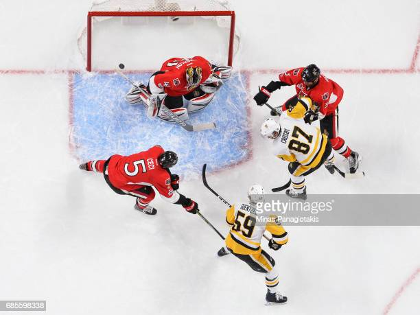 Goaltender Craig Anderson of the Ottawa Senators makes a save while teammates Cody Ceci and Marc Methot defend against Jake Guentzel and Sidney...